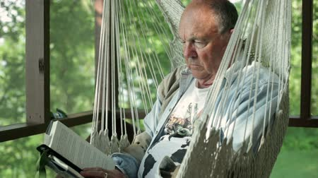 семидесятые годы : Senior man reading a book, while sitting in a hammock chair in a screen porch.