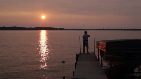 fenerbalığı : Senior man, fly-fishing (casting) off the end of a dock during a summer sunset. Footage shot off of Big Birch Lake in Minnesota, USA Stok Video