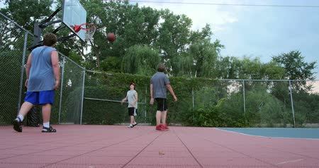 баскетбол : Young boys playing basketball in a small park. 4K Стоковые видеозаписи