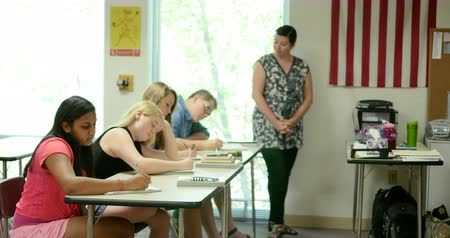 ödev : High school students taking notes and doing their assignments in classroom quietly, while teacher monitors. Ultra HD 4K