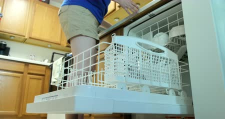 dirty : Young woman filling a dishwasher with dirty dishes. Ultra HD 4K