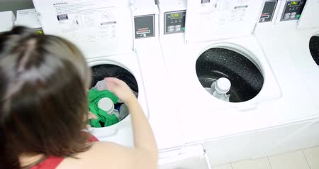çamaşırhane : Young woman washing her clothes and doing laundry in a laundromat. 4K Stok Video