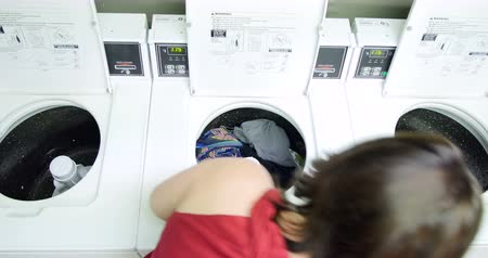 sıkıcı iş : Young woman washing her clothes and doing laundry in a laundromat. 4K Stok Video
