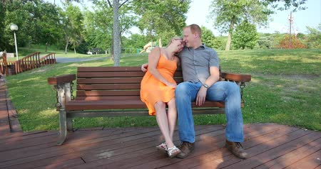 Young couple, in love, sitting on a park bench together on a late summer (early fall) day. 4K