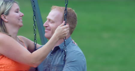 Young couple, in love, sitting on swings in a park playground together on a late summer (early fall) day. 4K