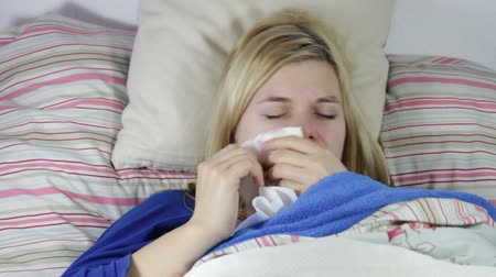 chřipka : Sick woman blowing nose and sneezing in bed.