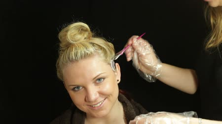 branqueamento : Woman and female hairdresser coloring her hair with brush Stock Footage