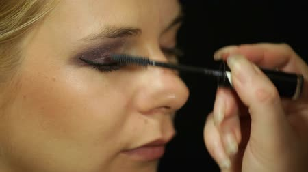 стегать : Detail of a young woman applying mascara eye makeup Стоковые видеозаписи