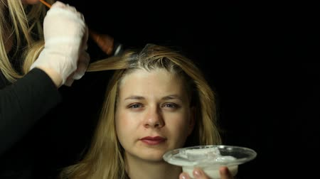белить : Woman at hairdresser bleaching hair