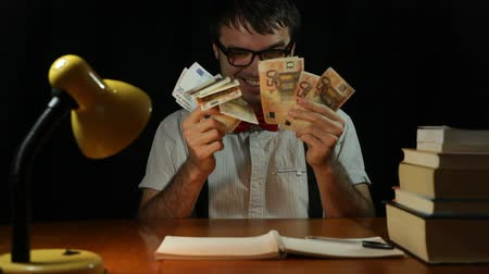 nerd : Funny ecstatic rich nerd man with euro banknotes in home office at night