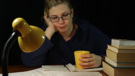 housecoat : Unhappy tired overworked woman in bathrobe drinking coffee in home office at night Stock Footage