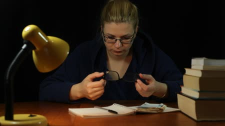 housecoat : Woman in bathrobe checking eyeglasses in home office at night
