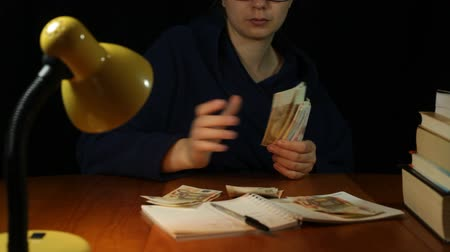 housecoat : Woman in bathrobe counting euro banknotes in home office at night Stock Footage