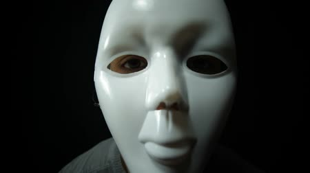 sobre o branco : Scary masked man over dark background Stock Footage