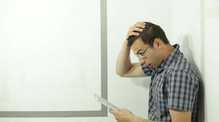 kötü : Shocked man leaning against wall and using tablet