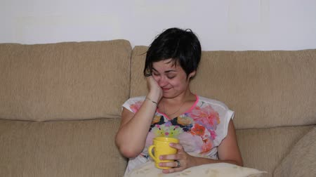 uykulu : Tired woman with hangover drinking coffee on sofa Stok Video