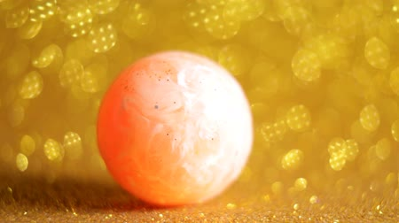 yuvarlanma : Rubber bouncing ball over glittering golden background Stok Video