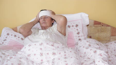 головная боль : Ill senior woman with headache in bed.