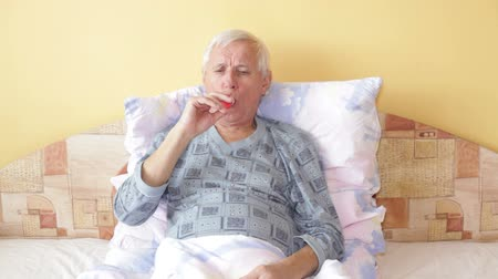 asthma : Senior man using asthma inhaler in bed. Stock Footage