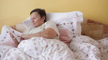 phablet : Senior woman using digital tablet in bed.