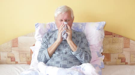 грипп : Sick senior man coughing and blowing his nose in bed.