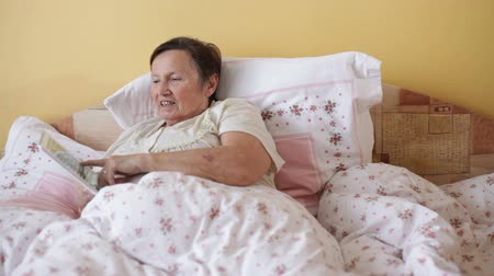 phablet : Happy senior woman using digital tablet in bed. Stock Footage