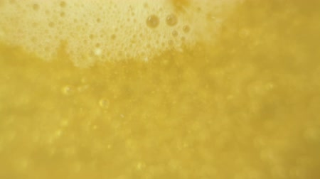 sparkling drink : Macro of carbon dioxide bubbles in yellow liquid.