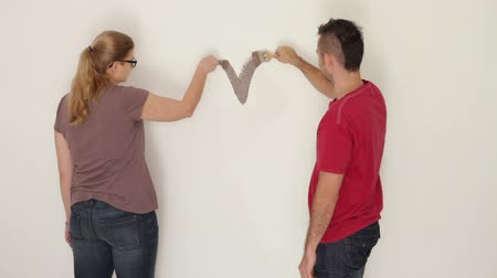 valentin nap : Happy couple in love painting heart shape on the wall. Stock mozgókép