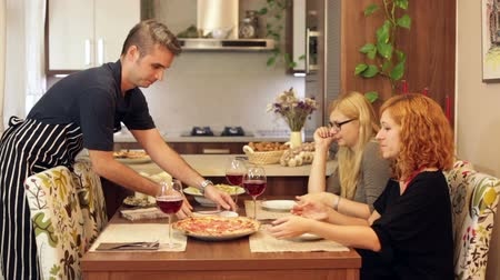 фастфуд : A man preparing pizza while two women sitting and eating behind the table at home. Стоковые видеозаписи