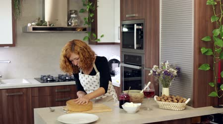 bıçak : Young happy woman cutting homemade cake in kitchen at home.