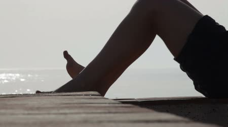 esneme : Silhouette of female legs stretching her feet and toes outdoors. Stok Video