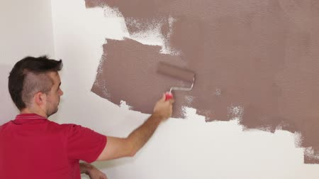 rolete : Man with paint roller painting white wall at interior using brown color.
