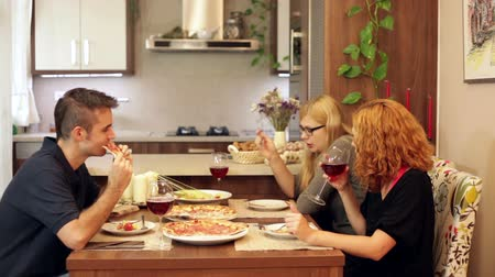 három ember : Group of friends eating pizza and drinking wine in dining room at home. Stock mozgókép