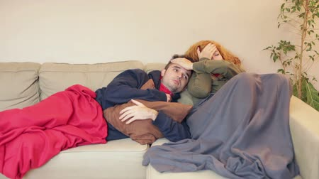 chřipka : Sleepy couple having a cold and resting together on the sofa at home.