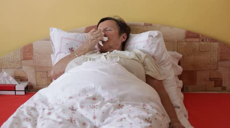 asthma : Ill senior woman blowing her nose in bed.