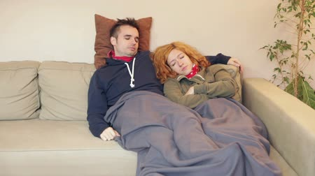 uykuda : Sleepy couple resting together on the sofa at home.