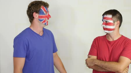 fósforo : Exited men with British and USA flags on faces competing, provoking and pushing against each other.