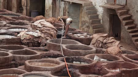 марокканский : Fes, Morocco - 18 July 2014: Chouara traditional leather tannery in Fez, Morocco. Стоковые видеозаписи