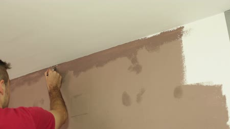pędzel : Man with a paint brush decorating interior. Wideo