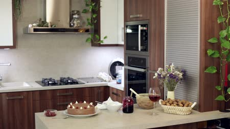 столовая : Homemade cake on the table and a woman walking through modern kitchen interior.