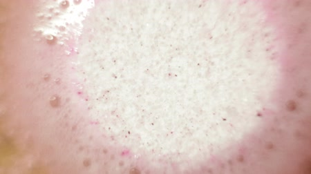 aqueous : Macro of pink effervescent tablet and carbon dioxide bubbling in the water. Stock Footage
