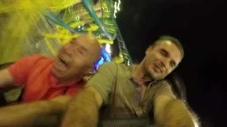řvát : Slow motion of excited people on the roller coaster ride in amusement park at night.