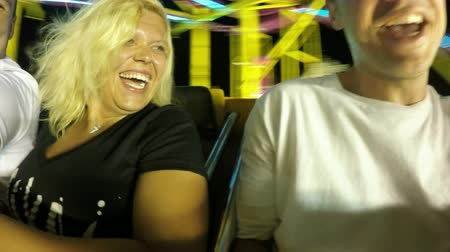ярмарка : Happy people enjoying roller coaster ride in amusement park at night.