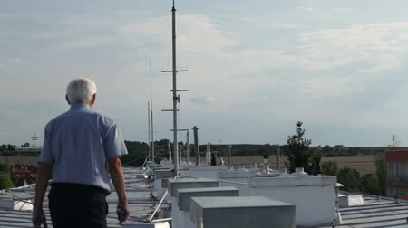 tin roofs : Senior man walking on the roof of a building and checking the rooftop surface.