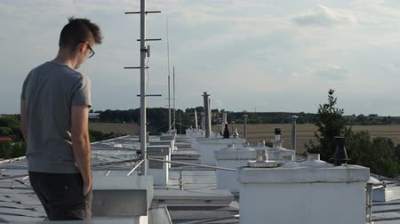 antennák : Young man walking on the rooftop of a building.