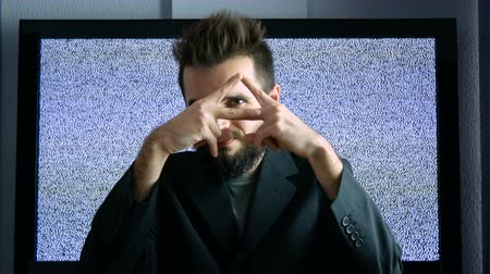 masonic : Bearded man in suit showing his eye in triangle as the Eye of Providence while moving forward and backwards with large grainy screen behind him.