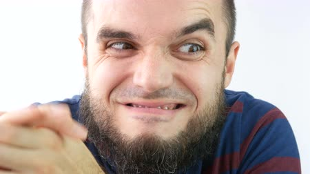 kezek : Closeup of greedy sly bearded man crazy giggling and rubbing his hands, studio isolated on white background.