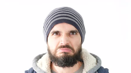 displeasure : Close-up of angry young bearded man in winter clothing frowning and looking at you, studio isolated on white background. Stock Footage