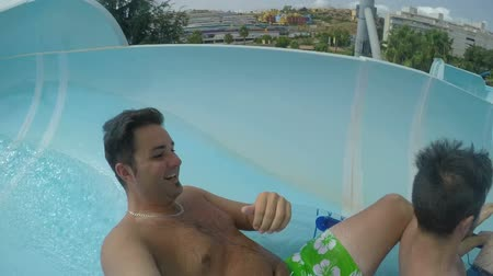 sürgülü : Slow-motion of happy people enjoying summer ride and sliding at waterpark.