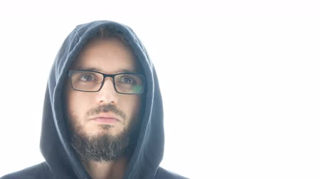 Close-up of bearded man in hoodie and eyeglasses shaking his head, studio isolated on white background.
